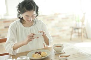 スマートフォンで撮影する若い女性の写真素材 [FYI01620888]