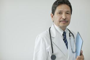 ファイルを持ち壁の前に立つ男性医師の写真素材 [FYI01620891]
