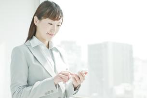 スマートフォンを操作するビジネスウーマンの写真素材 [FYI01620907]