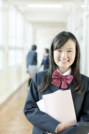 廊下に立ち笑顔の女子高校生の写真素材 [FYI01620935]
