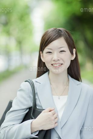 並木道を歩く笑顔のビジネスウーマンの写真素材 [FYI01620938]