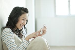 スマートフォンを操作する若い女性の写真素材 [FYI01620952]