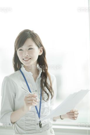 書類を持ち考える笑顔のビジネスウーマンの写真素材 [FYI01620964]