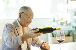 ワインをグラスにそそぐシニア男性の写真素材 [FYI01620968]