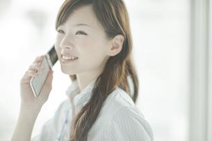 笑顔で携帯電話をかけるビジネスウーマンの写真素材 [FYI01620970]