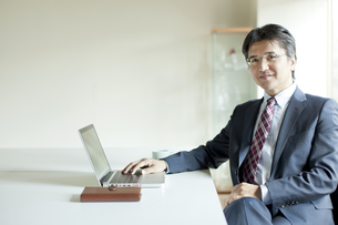 座りパソコンを見るビジネスマンの写真素材 [FYI01620971]