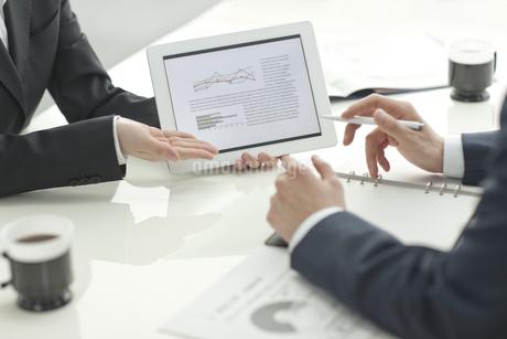 タブレットPCで打ち合せするビジネスマンとビジネスウーマンの写真素材 [FYI01620986]