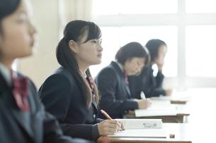 教室で真剣に授業を受ける女子校生の写真素材 [FYI01620987]