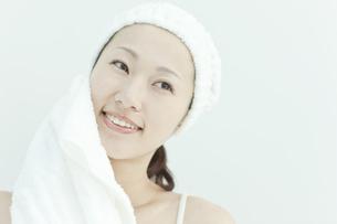 タオルで顔をふく若い女性のスキンケアイメージの写真素材 [FYI01620989]