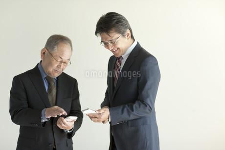 スマートフォンを操作する2人のビジネスマンの写真素材 [FYI01620991]