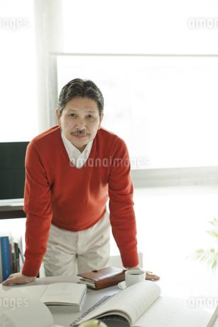 デスクに手をつくシニア男性の写真素材 [FYI01621025]