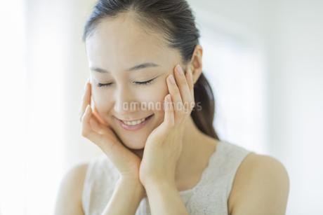 潤いを実感し微笑むスキンケアイメージの写真素材 [FYI01621028]