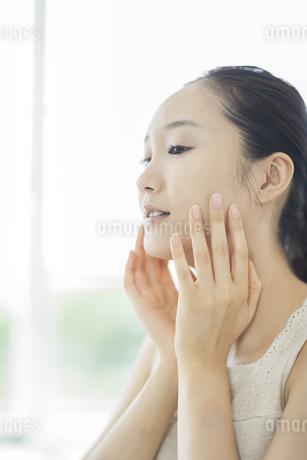 潤いを実感し微笑むスキンケアイメージの写真素材 [FYI01621029]