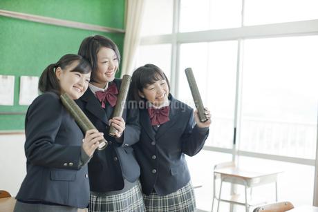 卒業証書を持つ笑顔の女子校生の写真素材 [FYI01621031]