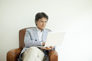 ソファーに座りノートPCを見るミドル男性の写真素材 [FYI01621036]
