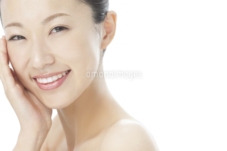 手を頬に添えて微笑む女性のスキンケアと美容イメージの写真素材 [FYI01621043]
