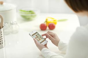 スマートフォンでレシピを見る若い女性の写真素材 [FYI01621050]