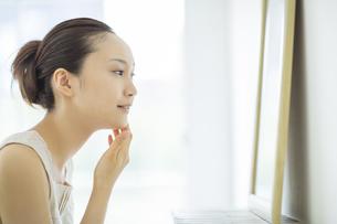 鏡を見て顔に手を触れるスキンケアイメージの写真素材 [FYI01621067]