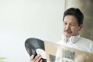 レコードをジャケットから出すシニア男性の写真素材 [FYI01621073]