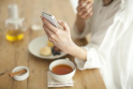 スコーンを食べながらスマートフォンを持つ女性の写真素材 [FYI01621087]