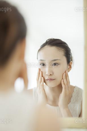 鏡を見て顔に手を触れるスキンケアイメージの写真素材 [FYI01621089]