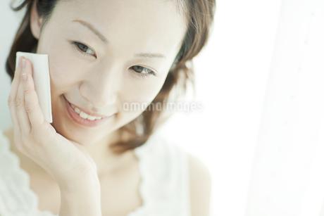 コットンを顔に置く女性 美容とスキンケアイメージの写真素材 [FYI01621104]