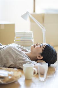 引っ越し作業中寝転ぶ女性の写真素材 [FYI01621113]