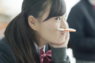 授業中鉛筆を口の上に乗せる女子校生の写真素材 [FYI01621118]