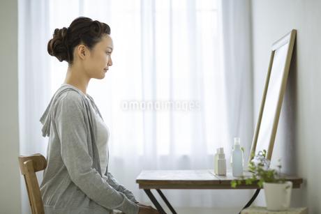 鏡を見る若い女性のスキンケアイメージの写真素材 [FYI01621121]