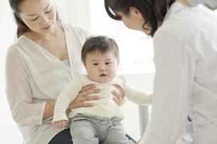 乳児の診察をする女性医師の写真素材 [FYI01621123]