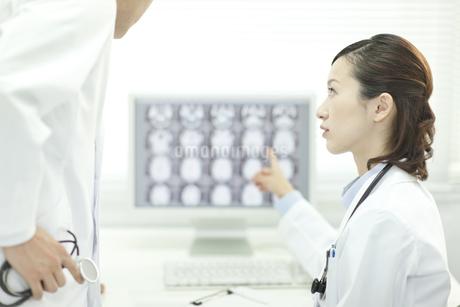 モニターの前で男性医師と話す女性医師の写真素材 [FYI01621128]