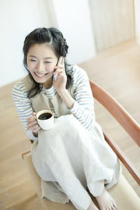 コーヒーを飲みながらスマートフォンで話す笑顔の若い女性の写真素材 [FYI01621144]