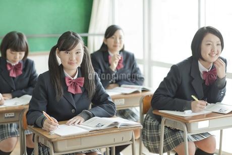 授業中先生の話を聞く笑顔の女子校生の写真素材 [FYI01621155]