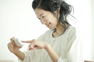 スマートフォンで撮影する若い女性の写真素材 [FYI01621169]