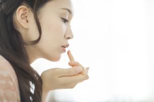 口紅を塗る美容イメージの写真素材 [FYI01621172]
