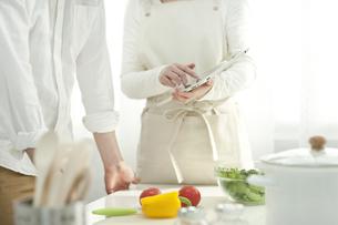 タブレットPCでレシピを調べる若い夫婦の写真素材 [FYI01621174]