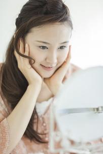 メイクの仕上がりを見る女性の写真素材 [FYI01621187]