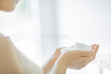 洗顔の泡を両手に持つスキンケアイメージの写真素材 [FYI01621198]