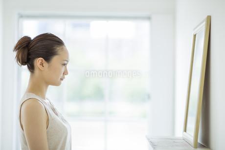 鏡を見る若い女性のスキンケアイメージの写真素材 [FYI01621211]