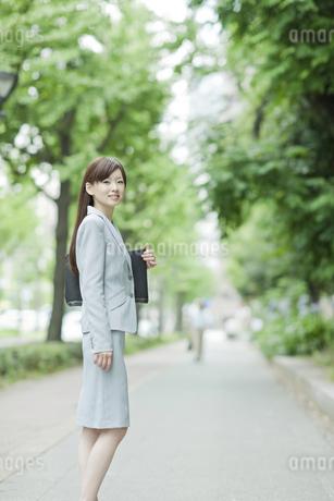 並木道で振り向くビジネスウーマンの写真素材 [FYI01621213]