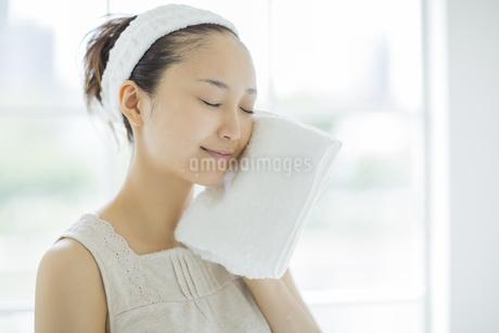 タオルで顔を拭くスキンケアイメージの写真素材 [FYI01621218]