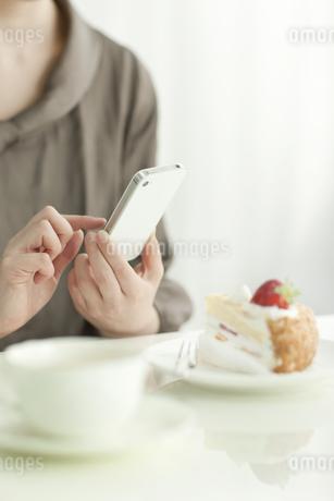 カフェでスマートフォンを操作する若い女性の写真素材 [FYI01621220]