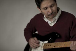 ギターを弾くシニア男性の写真素材 [FYI01621226]