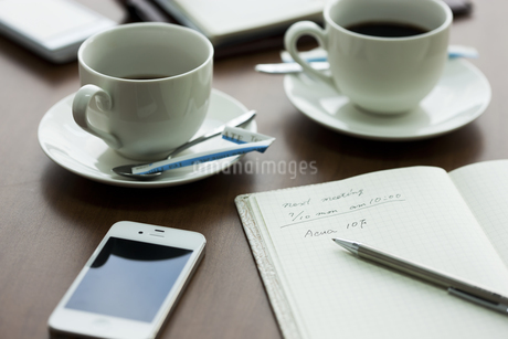 テーブルに置かれたスマートフォンとノートとコーヒーの写真素材 [FYI01621228]