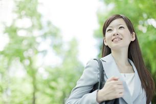 並木道を歩く笑顔のビジネスウーマンの写真素材 [FYI01621237]