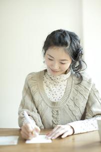 年賀状を書く若い女性の写真素材 [FYI01621260]