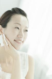 コットンを顔に置く女性 美容とスキンケアイメージの写真素材 [FYI01621261]