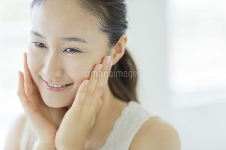 潤いを実感し微笑むスキンケアイメージの写真素材 [FYI01621266]