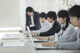 デスクワークのビジネスマンとビジネスウーマンの写真素材 [FYI01621280]