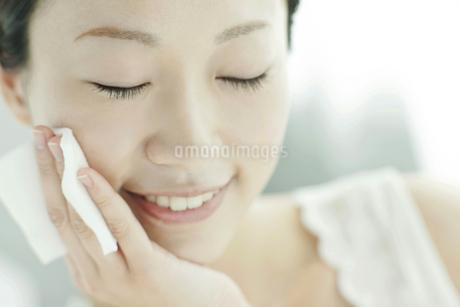 コットンを頬にあて喜ぶ若い女性の写真素材 [FYI01621283]